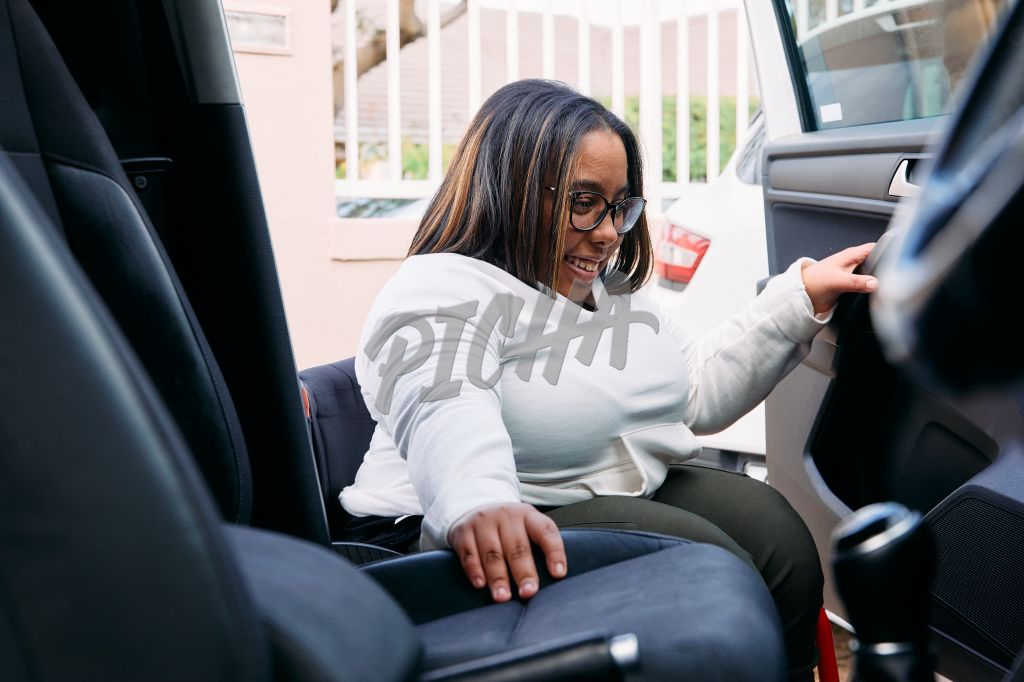 Young Woman with a disability getting into the car