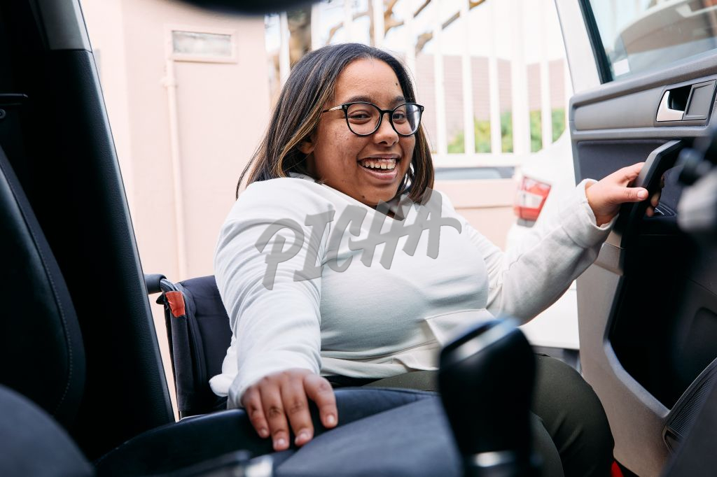 Young Woman with a disability smiling whilst going into her car