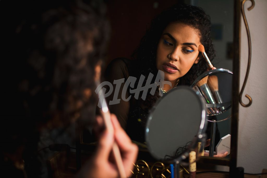 Young creative uses mirror to touch up makeup