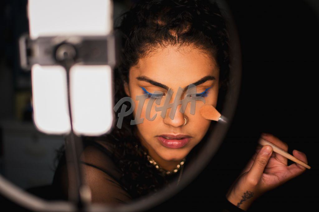 Creative touches up her face with a makeup brush