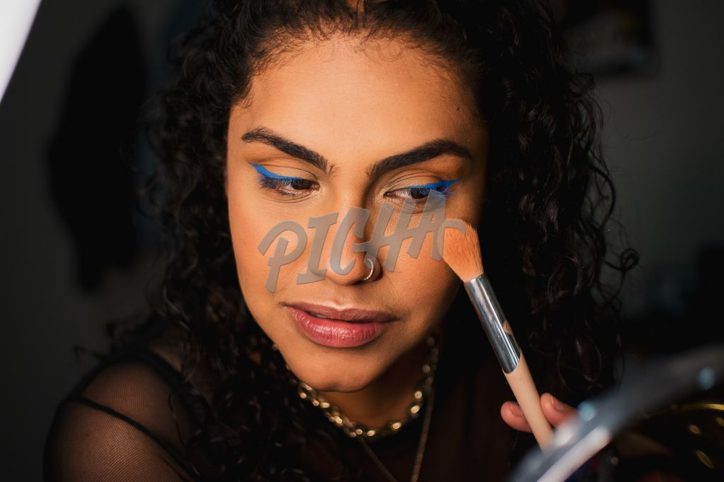 Young lady applies some foundation with a makeup brush