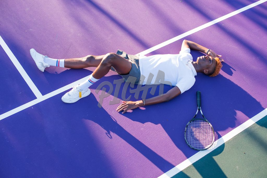Young man laying on purple coloured tennis court
