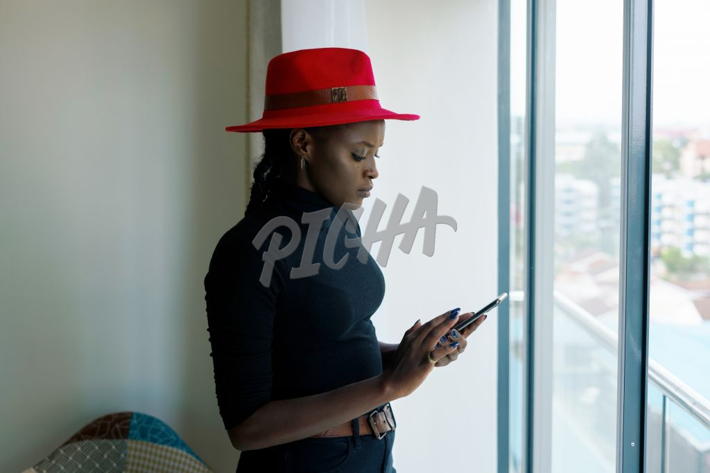 woman in red hat checking her phone