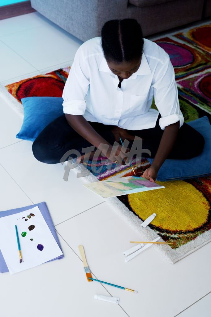 Lady works on a painting while seated on a carpet