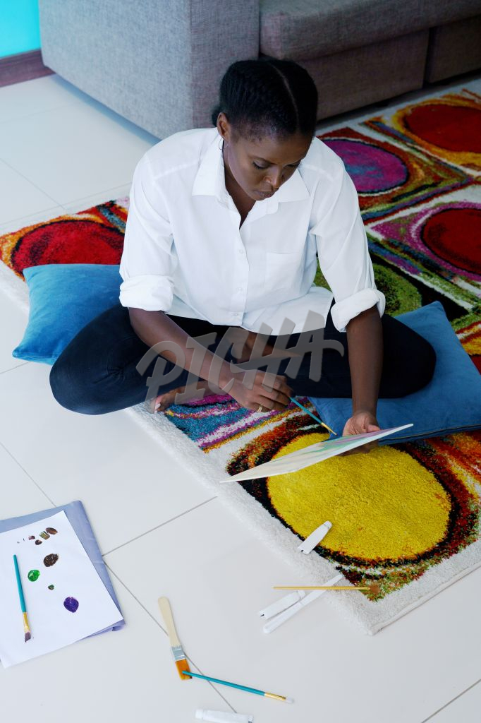 Lady paints while seated on the floor