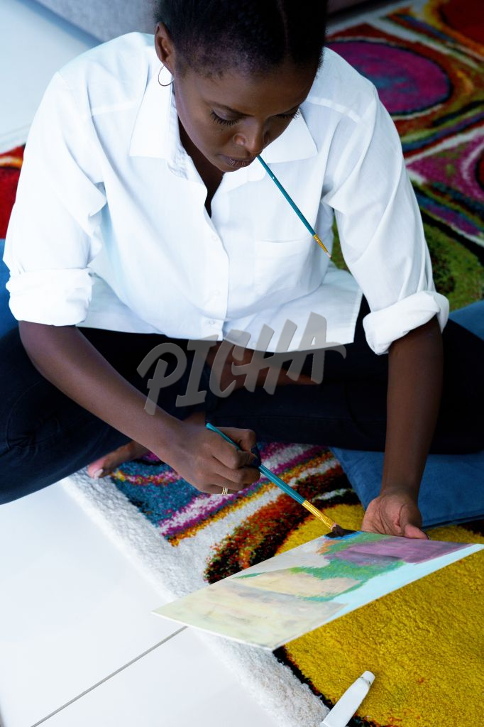 Lady works on a painting from the carpet