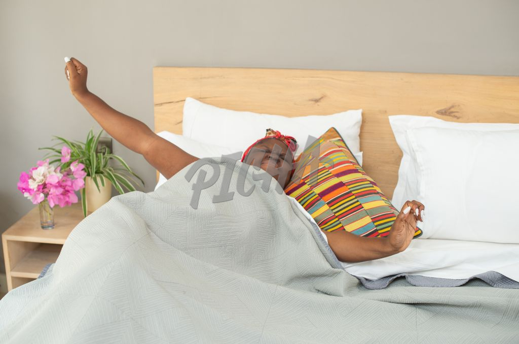 Woman in headscarf stretching in bed