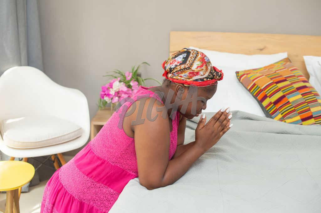 Lady says a prayer by the bedside