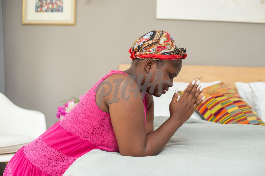 Woman kneels by bedside to say prayer