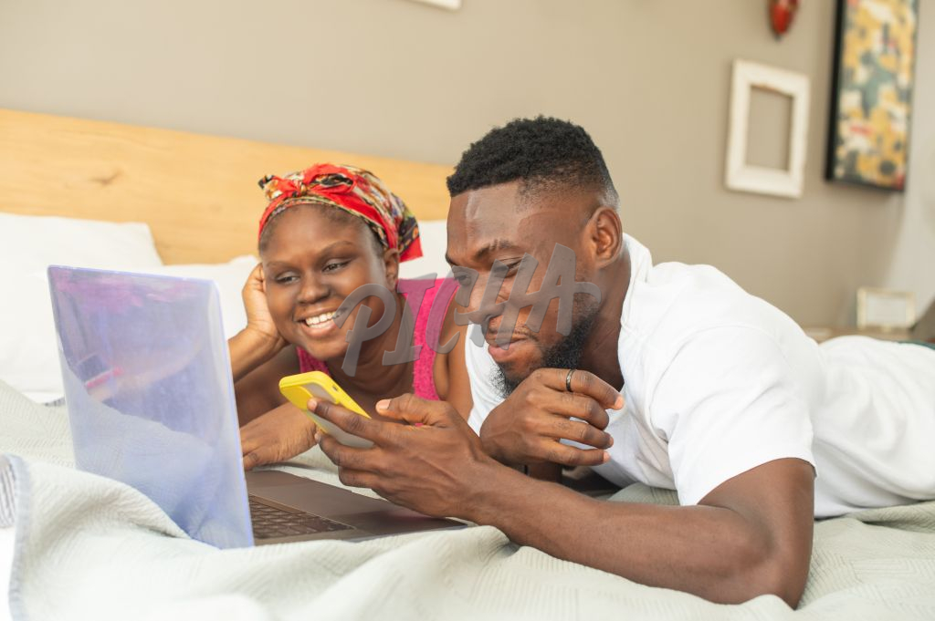 Couple have fun on their devices at bedtime