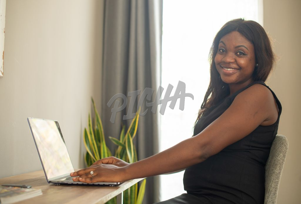 Woman looks away from laptop and smiles