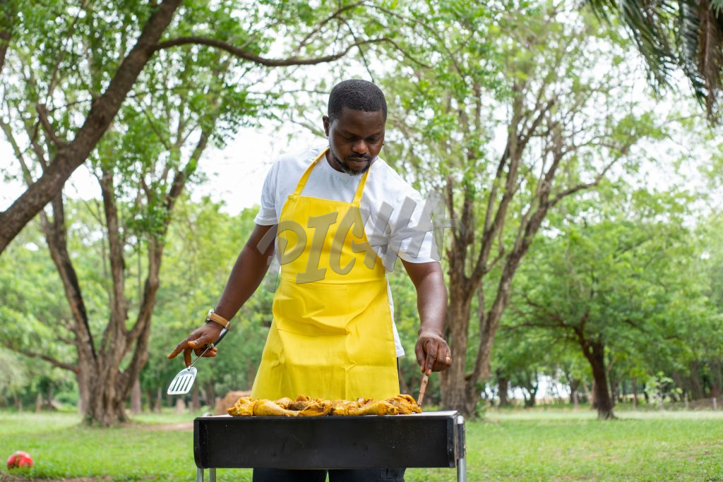 man wearing an apron grilling outdoors