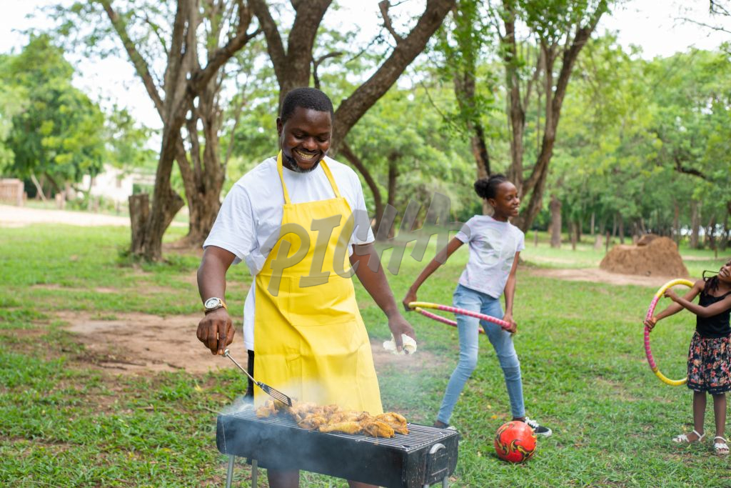 Black Man Grilling chicken outdoor with girls playing hula hoop