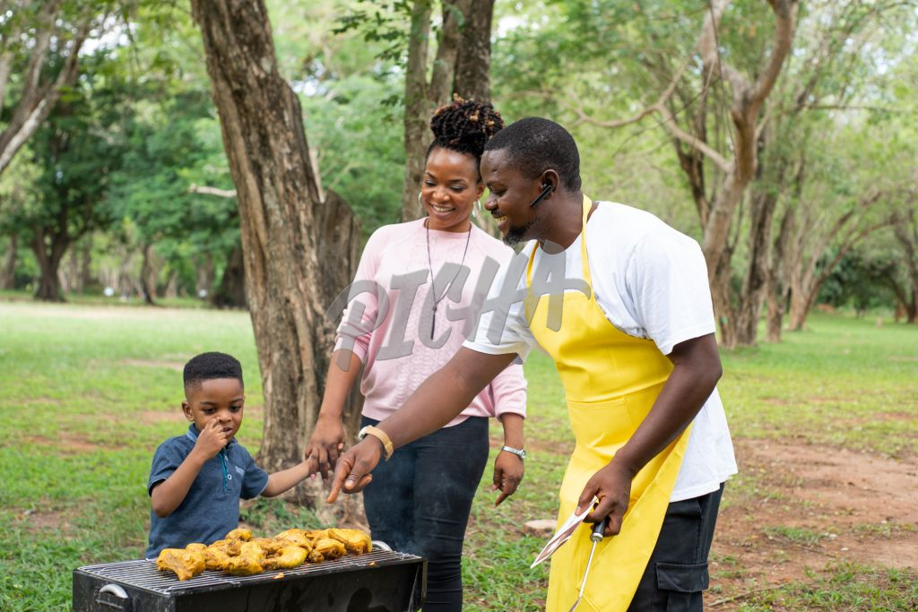 Man Grilling outdoors with family
