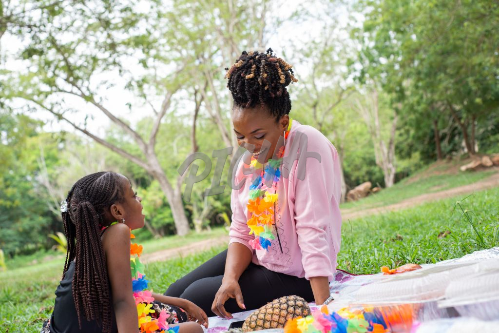 Black mother and daughter sitting in a park