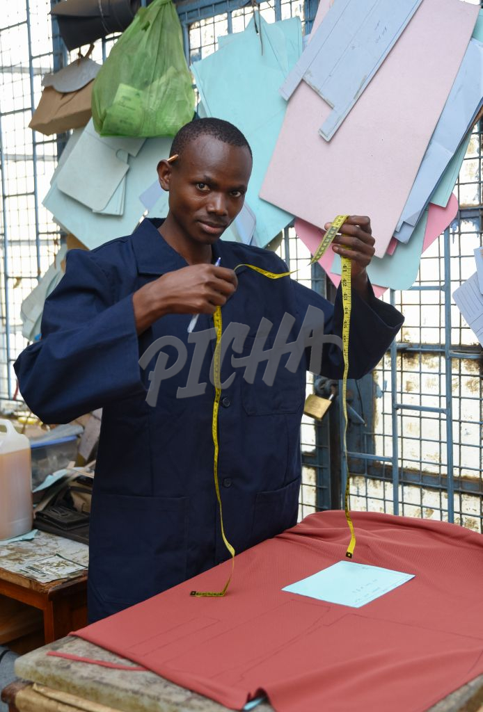 Man preparing to measure fabric with a tape measure