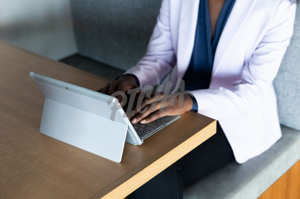 Black woman typing on a surface tablet