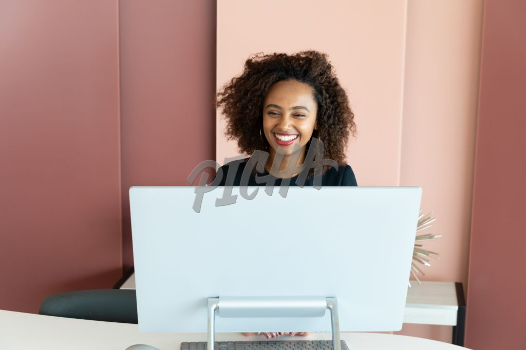 smiling woman sitting behind a computer