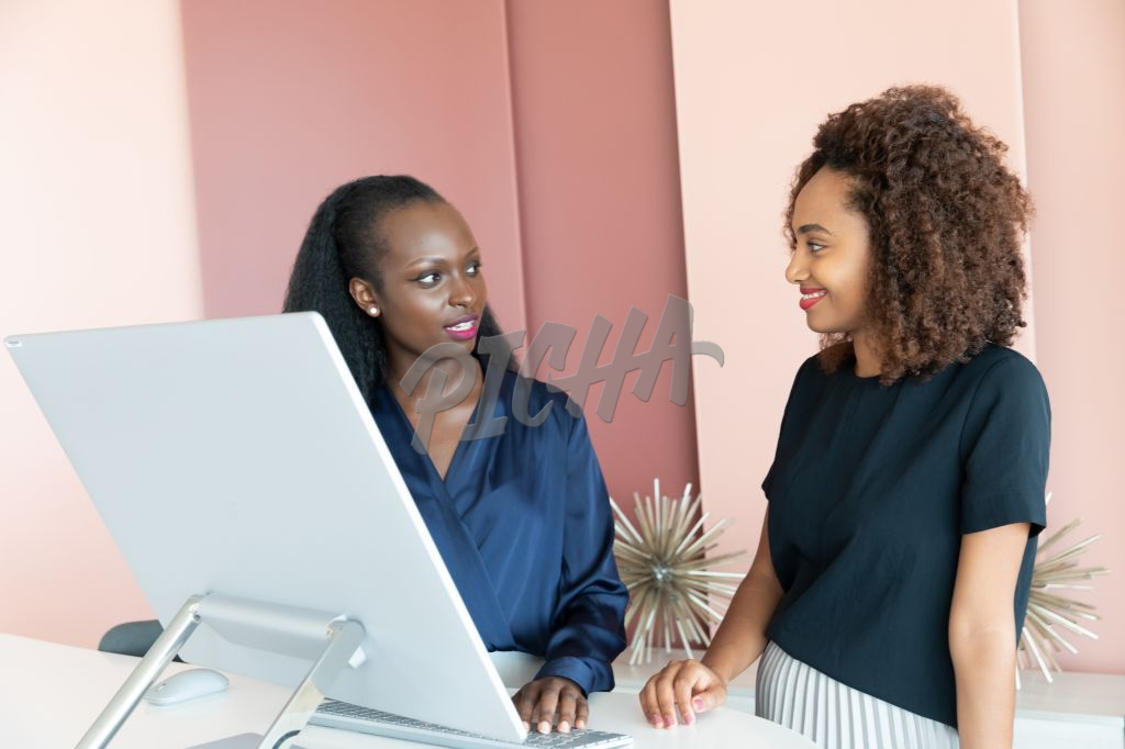 two bkack women standing behind a comouter monitor at work