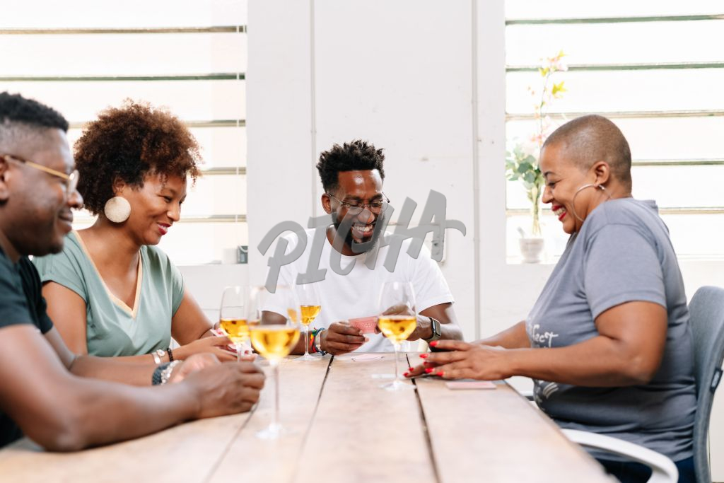 Friends having wine and playing cards