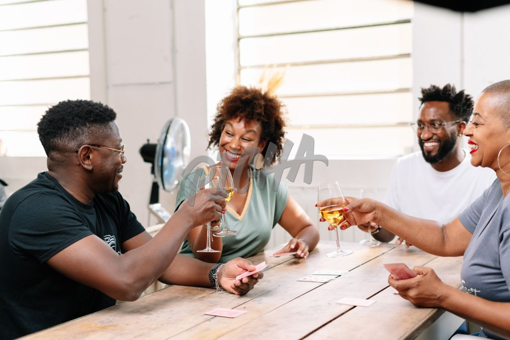 Friends enjoy wine and a game of cards