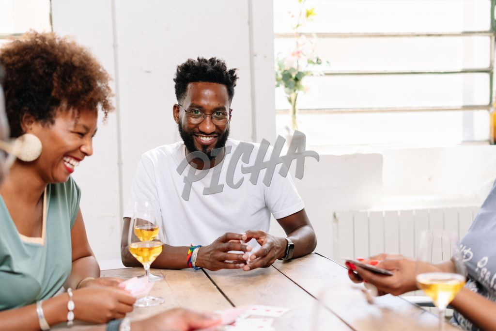 Friends having play a card game while enjoying a drink
