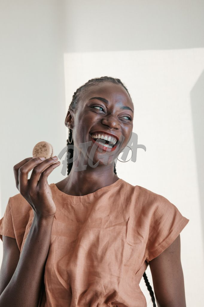 woman laughs with cookie in hand