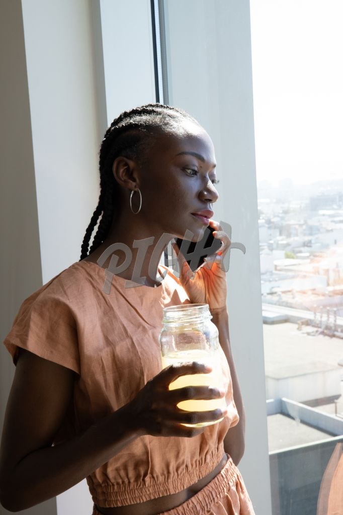 woman holds jar of juice during phone call