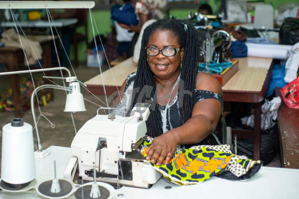 Woman With Disability happy at work sewing clothes